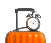 Alarm clock on orange suitcase — Stock Photo