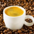 Cup of espresso in coffee beans — Stock Photo
