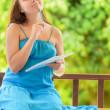 młoda kobieta, w piśmie do notebooka. zewnątrz portret — Zdjęcie stockowe