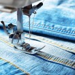 Stock Photo: Sewing machine and jeans fabric