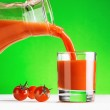 Tomato juice pouring from jug into a glass — Stock Photo