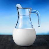 罐牛奶的天空背景上。半满满的水罐 — 图库照片