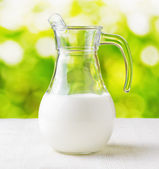 罐牛奶对自然背景。半满满的水罐 — 图库照片