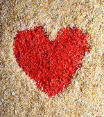 Red heart sign in yellow sand — Stock Photo