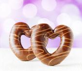Chocolate hearts on purple backgroud — Stock Photo