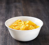 Bowl of cornflakes on wooden table — Foto de Stock