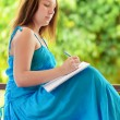 Young woman writing to notebook. Outdoor portrait — Stock Photo