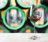 Glass of wine and wooden barrels in winery — Stock Photo