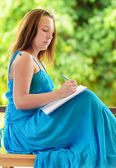 Young woman writing to notebook. Outdoor portrait — Stok fotoğraf