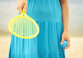 Woman in blue dress playing tennis on the beach — Stock Photo