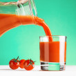 Tomato juice pouring from jug into a glass — Stock Photo #39599753