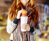 Young woman holding a tumbler of coffee — Stock Photo