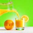 Orange juice pouring from jug into a glass — Stock Photo