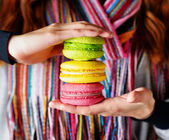 Young woman holding the french pastry macaron in cafe — Stock Photo