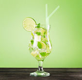 Glass of mojito cocktail on pastel green background — Stock Photo