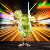 Glass of mojito cocktail on city background — Stock Photo