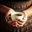 Hands of senior woman holding cup of coffee — Stock Photo