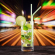 Стоковое фото: Glass of mojito cocktail on city background