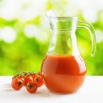 Jug of tomato juice on nature background. Half full pitcher — Stock Photo