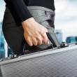 Business woman holding an aluminium briefcase — Stock Photo