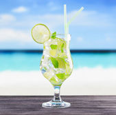 Glass of mojito cocktail on a beach — Stock Photo