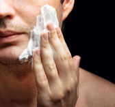 Young man applying a shaving foam — Stock Photo