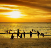 Group of people on sunset beach — Stock Photo