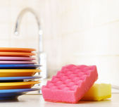 Several plates and a kitchen sponge. Dishwashing concept — Stock Photo