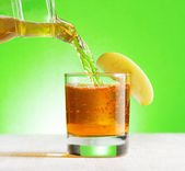 Apple juice pouring from jug into a glass — Stock Photo