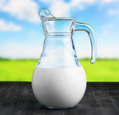 Jug of milk on meadow background. Half full pitcher — Stock Photo