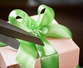 Decorating gift box with green ribbon using scissor — Foto Stock
