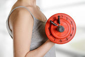 Beginner female athlete holding dumbbell with clock dial. Time f — Stock Photo