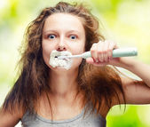 Shaggy young woman using electric toothbrush — Stock Photo