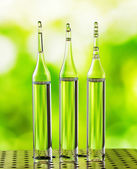 Three ampoules on nature background — Foto Stock