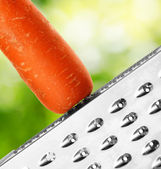 Ripe carrot rubbing on a grater — Stock Photo