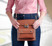 Young woman in deep blue jeans holding a bag — Stockfoto