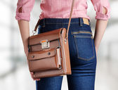 Young woman in deep blue jeans holding a bag — Stock Photo