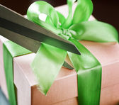 Decorating gift box with green ribbon using scissor — Stock Photo