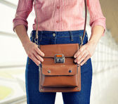 Young woman in deep blue jeans holding a bag — Foto de Stock