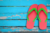 Red ang green flip flop sandals on blue wood — Stock Photo