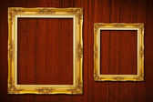 Golden frame on wood background — Stock Photo