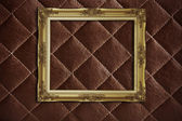 Golden frame on red leather — Stock Photo