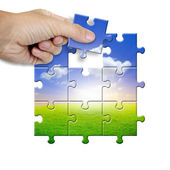 Hand collecting a part of a landscape puzzle — Stock Photo