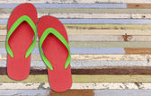 Red and green flip flop sandals on old painting wood  — Stock Photo