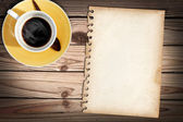 Old note paper on wood table with a cub of coffee — Stockfoto