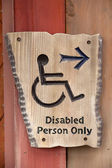 A handicapped sign on wood wall  — Stock Photo