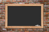 Blackboard on old brick wall background — Stock Photo
