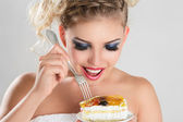 Beautiful blonde woman eating a cake — Stock Photo