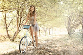 Young woman with bicycle in a park — Stock Photo