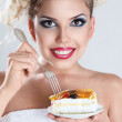 Beautiful blonde woman eating a cake - Stock Photo